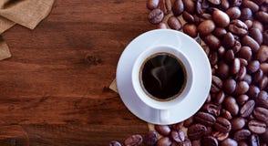Koffiekop en koffiebonen op houten lijst uitstekende stijl als achtergrond voor grafisch ontwerp stock fotografie