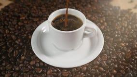 Koffiekop en koffiebonen Witte kop van verdampende koffie op de lijst met geroosterde boon Voorraadlengte stock videobeelden