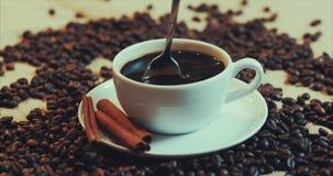 Koffiekop en koffiebonen Witte kop van verdampende koffie op de lijst met geroosterde boon Voorraadlengte 4K stock video