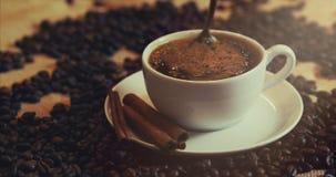 Koffiekop en koffiebonen Witte kop van verdampende koffie op de lijst met geroosterde boon Voorraadlengte 4K stock videobeelden