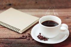 Koffiekop en notaboek Stock Foto's