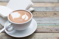 Koffiekop en notitieboekje op grungeachtergrond Stock Afbeeldingen