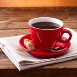 Koffiekop en schotel op tafelkleed op houten lijst Donkere achtergrond Het concept van de koffie Selectieve nadruk Stock Foto's