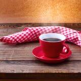Koffiekop en schotel op tafelkleed op houten lijst Donkere achtergrond Het concept van de koffie Selectieve nadruk Stock Afbeeldingen