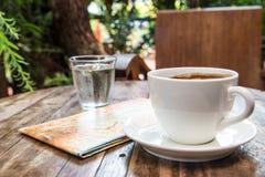 Koffiekop, kaart, Glaswater op houten lijst Slechte lichte achtergrond Stock Foto's