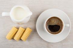 Koffiekop, melk in kruik, wafeltjebroodjes op houten lijst royalty-vrije stock foto