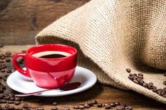Koffiekop met coffeebeans en jutetextiel Stock Foto's