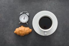 koffiekop met croissant en wekker Stock Fotografie