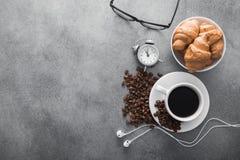 koffiekop met croissant en wekker, zwarte glazen Stock Foto's