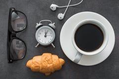 koffiekop met croissant en wekker, zwarte witte glazen, Stock Foto