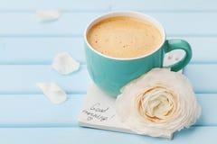 Koffiekop met de lentebloem en nota'sgoedemorgen op blauwe rustieke achtergrond, ontbijt Stock Afbeelding