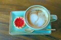 koffiekop met hartvorm met aardbeikoekje op blauwe plat royalty-vrije stock foto