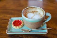 koffiekop met hartvorm met aardbeikoekje op blauwe plat stock foto's