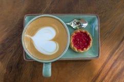 koffiekop met hartvorm met aardbeikoekje op blauwe plat royalty-vrije stock fotografie