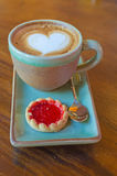 koffiekop met hartvorm met aardbeikoekje op blauwe plat stock afbeelding