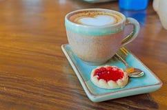 koffiekop met hartvorm met aardbeikoekje op blauwe plat Royalty-vrije Stock Foto's