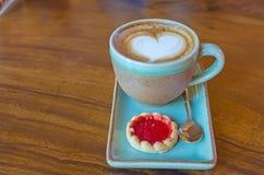 koffiekop met hartvorm met aardbeikoekje op blauwe plat Stock Foto