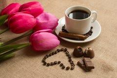 Koffiekop met koffiebonen op jute en roze tulpen Royalty-vrije Stock Foto