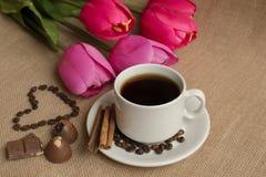 Koffiekop met koffiebonen op jute en roze tulpen Royalty-vrije Stock Afbeelding