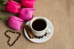 Koffiekop met koffiebonen op jute en roze tulpen royalty-vrije stock afbeeldingen
