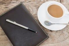 Koffiekop met notaboek op houten achtergrond Stock Afbeelding