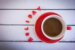 Koffiekop met rode kleiteksten op houten lijst Stock Foto's