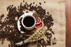 Koffiekop met ruwe bonen op jute stock afbeelding
