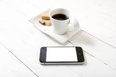 Koffiekop met wafeltje en telefoon stock fotografie