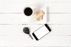 Koffiekop met wafeltje, telefoon, autosleutel stock afbeelding