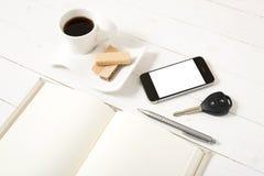 Koffiekop met wafeltje, telefoon, autosleutel, notitieboekje stock fotografie