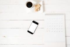 Koffiekop met wafeltje, telefoon, kalender royalty-vrije stock fotografie