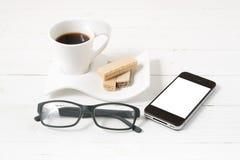 Koffiekop met wafeltje, telefoon, oogglazen royalty-vrije stock foto