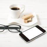 Koffiekop met wafeltje, telefoon, oogglazen stock afbeeldingen