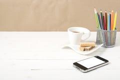 Koffiekop met wafeltje, telefoon, potlooddoos royalty-vrije stock afbeelding