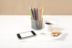 Koffiekop met wafeltje, telefoon, potlooddoos royalty-vrije stock foto