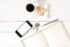 Koffiekop met wafeltje, telefoon, sleutel, notitieboekje stock fotografie