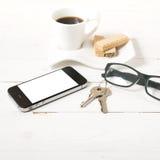 Koffiekop met wafeltje, telefoon, sleutel, oogglazen royalty-vrije stock fotografie