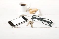 Koffiekop met wafeltje, telefoon, sleutel, oogglazen stock foto
