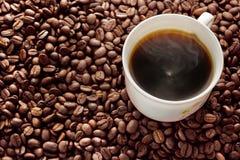 Koffiekop op de achtergrond van koffiebonen. Royalty-vrije Stock Afbeelding