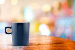 Koffiekop op houten lijst bij onduidelijk beeld bokeh achtergrond Royalty-vrije Stock Afbeeldingen