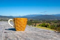 Koffiekop op houten lijst met blauwe hemel en mooie berg royalty-vrije stock afbeelding
