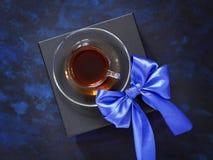 Koffiekop in zwarte giftdoos en een boog van blauw lint Stock Afbeeldingen