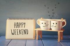 koffiekoppen naast notitieboekje met uitdrukkings gelukkig weekend Royalty-vrije Stock Fotografie