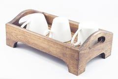 Koffiekoppen op houten dienblad op witte achtergrond Stock Fotografie