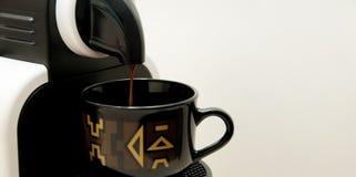Koffiemachine die het sterke kijken gieten verse koffie in een keurige ceramische kop Stock Afbeeldingen
