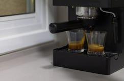 Koffiemachine die koffie in twee glaskoppen produceren op een keukenlijst stock fotografie
