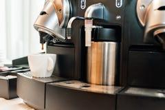 Koffiemachine het gieten in witte kop Stock Foto's