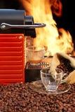 Koffiemachine met twee koppen van espresso en brandachtergrond Stock Foto's