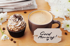 Koffiemok met cupcake, bloemen, krant en nota'sgoedemorgen op rustieke lijst, zoet dessert voor ontbijt Stock Fotografie
