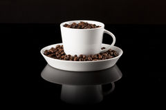 Koffiemok met koffie op zwarte weerspiegelende oppervlakte wordt gevuld die stock fotografie